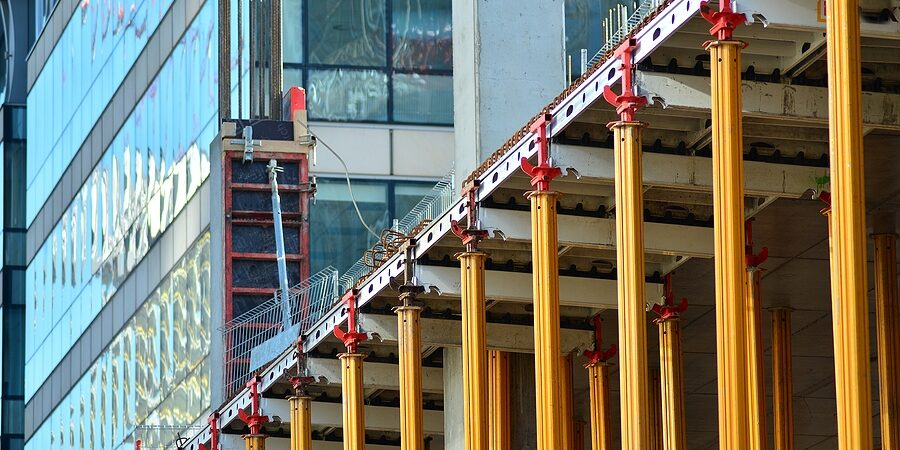 concrete pillars on construction site. building of skyscraper with crane, tools and reinforced steel bars.