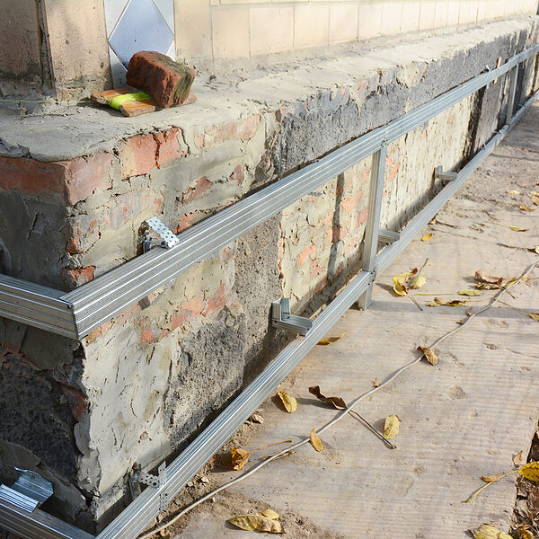house foundation wall repair, renovation with installing metal sheets on metal frame for waterproofing and protect from wetness.